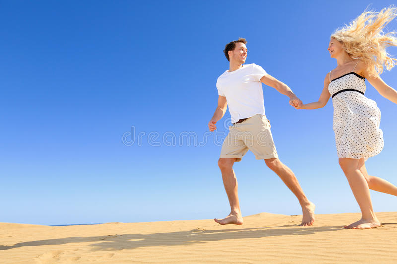 Happy couple in playful and romantic relationship. Having fun under sun and blue sky in desert. Two young lovers running cheerful together on romance in summer stock image