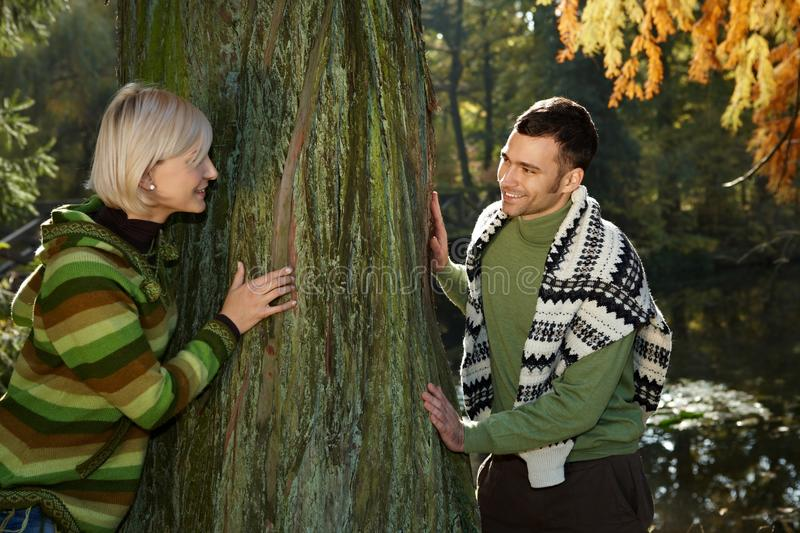 Happy couple playing catch me around tree outdoor. Happy casual caucasian couple playing catch me around tree outdoor at autumn forest. Having fun, hiking royalty free stock photography