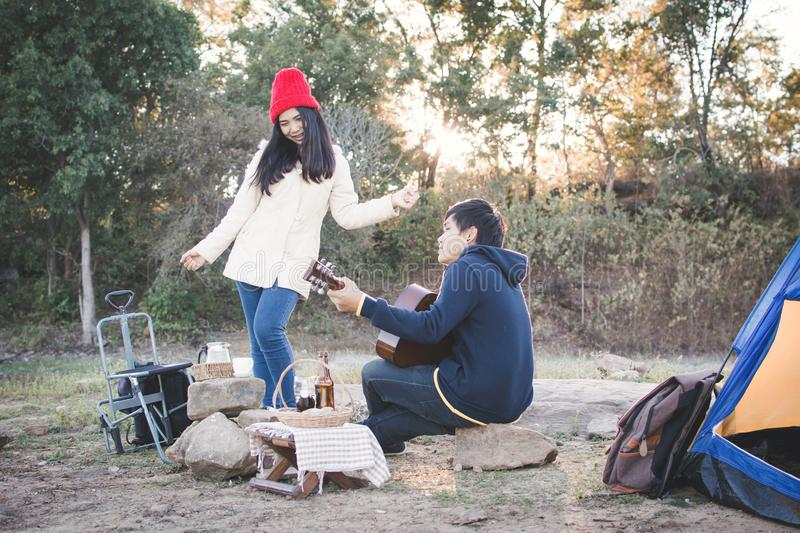 Happy couple playing guitar in nature winter season. Relax time on holiday concept travel and camping partnership,selective and soft focus,tone of hipster style stock image