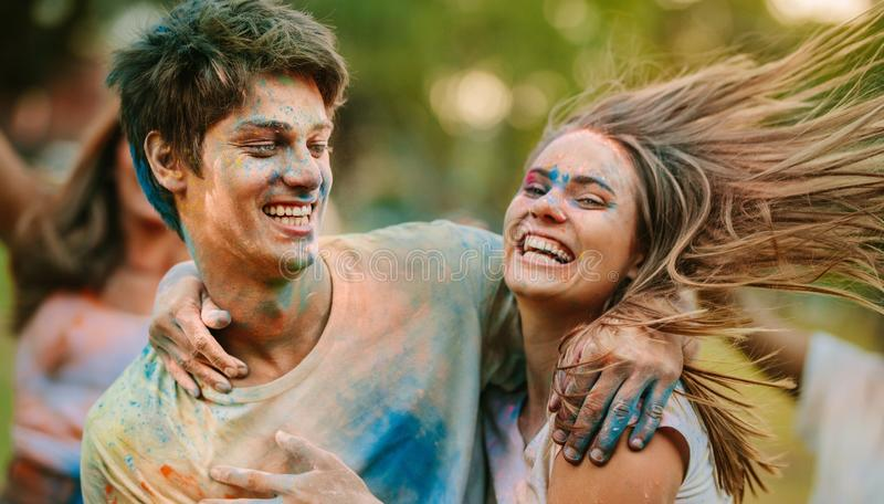 Happy couple playing holi together and having fun stock photo