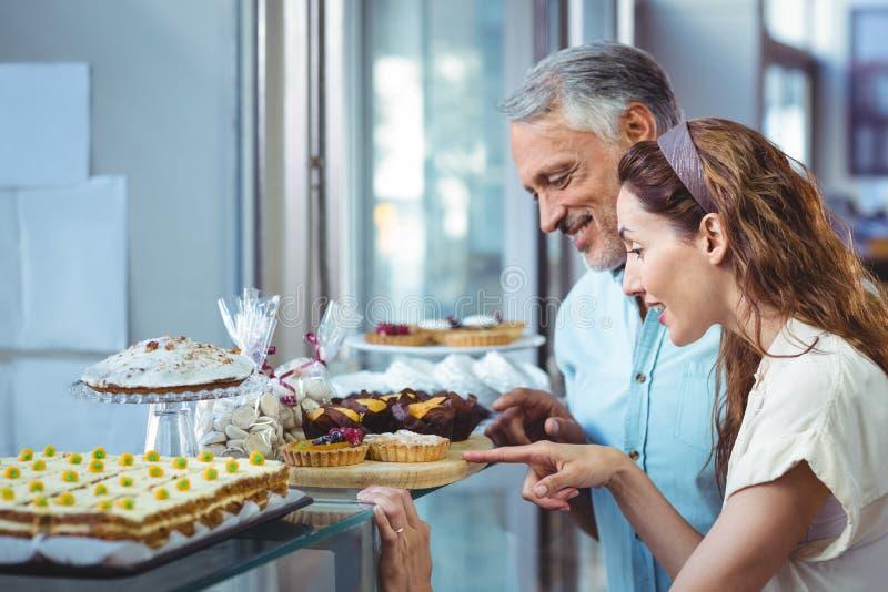 Happy couple pointing cakes stock photos