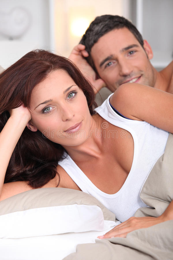 Happy couple posing in bed royalty free stock image