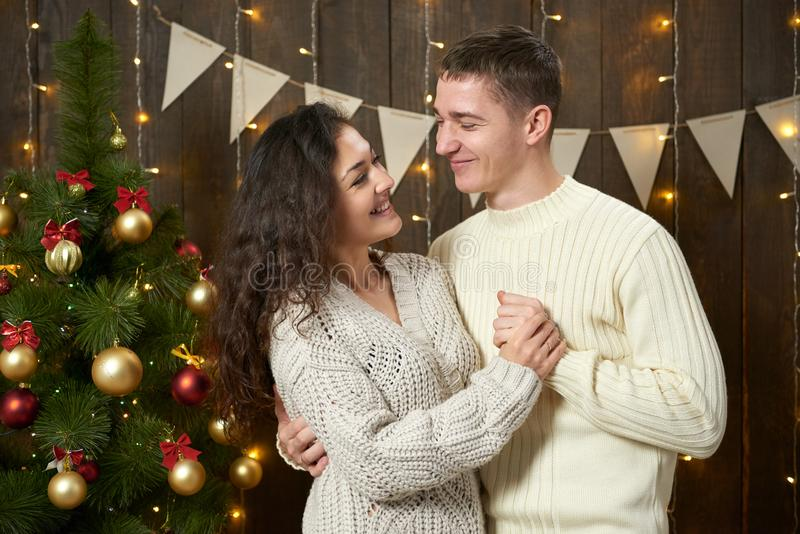 Happy couple posing in christmas decoration, dark wooden interior with lights. Romantic evening and love concept. New year holiday royalty free stock photos