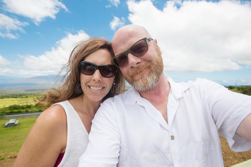 Middle aged couple with heads touching under bright blue sky. Happy couple posing for a selfie royalty free stock photography