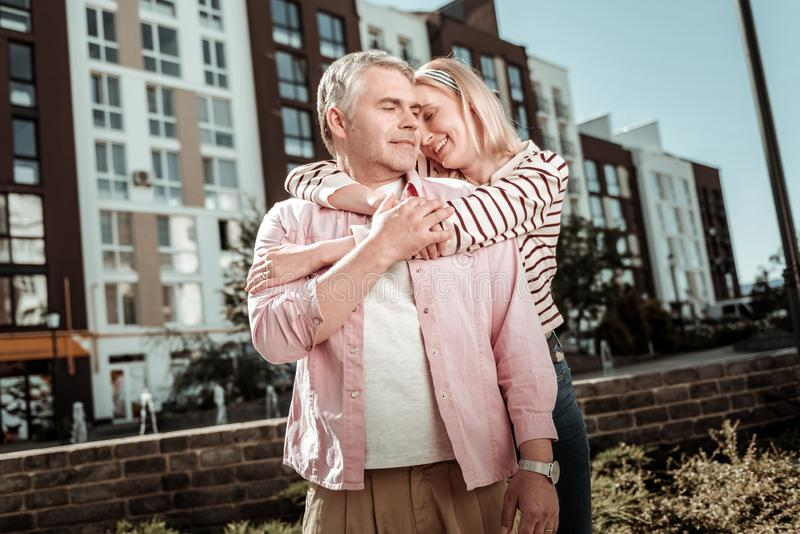 Positive blonde young woman hugging her husband royalty free stock image