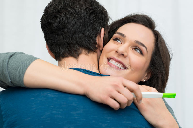 Happy couple with a pregnancy test. Closeup of happy young women embracing men after positive pregnancy test royalty free stock images