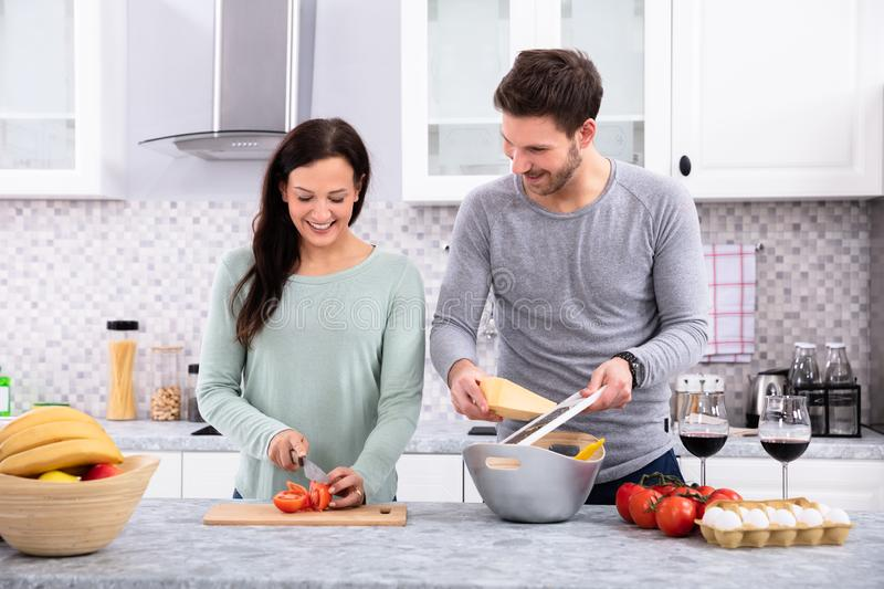 Happy Couple Preparing Food In Kitchen. Husband Looking His Wife While She Is Cutting Tomato On Chopping Board In Kitchen royalty free stock image
