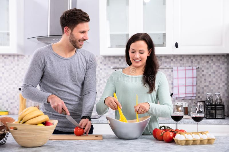 Happy Couple Preparing Food In Kitchen. Husband Looking His Wife While Cutting Tomato On Wooden Chopping Board With Knife In Kitchen royalty free stock images