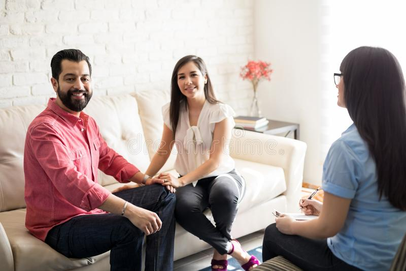 Happy couple and psychologist in the office. Happy hispanic married couple visiting psychologist for counseling royalty free stock photography