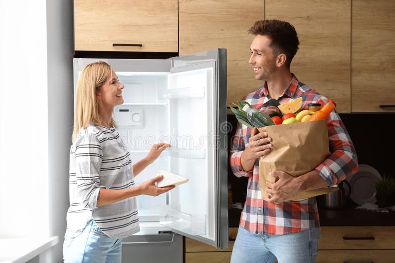 Happy couple putting products into refrigerator stock photo