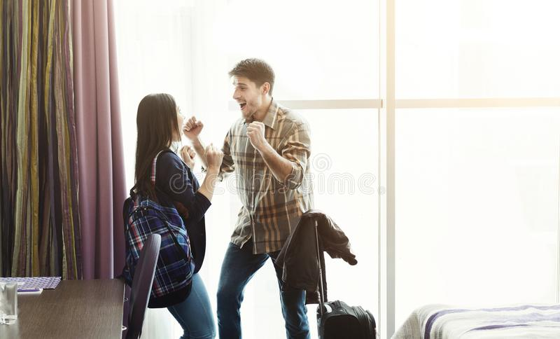 Happy couple arriving in hotel room on holidays stock images