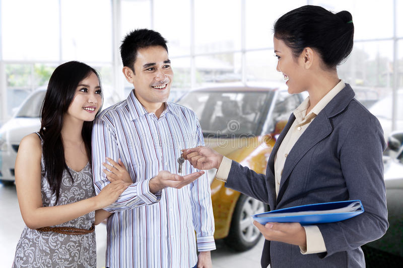 Happy couple receive a car key royalty free stock image