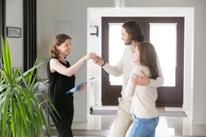 Happy couple receiving house keys from realtor royalty free stock image