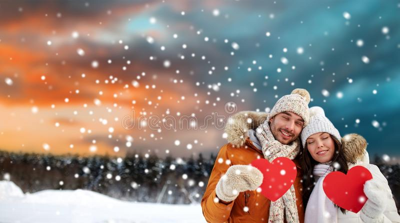 Happy couple with red hearts over winter landscape stock photos