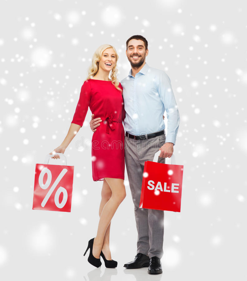 Happy couple with red shopping bags over snow. People, sale, christmas, winter and holidays concept - happy couple with red shopping bags hugging over snow royalty free stock photos