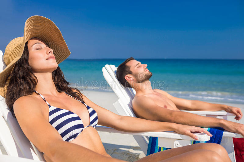 Happy couple relaxing on deck chair at the beach royalty free stock photos