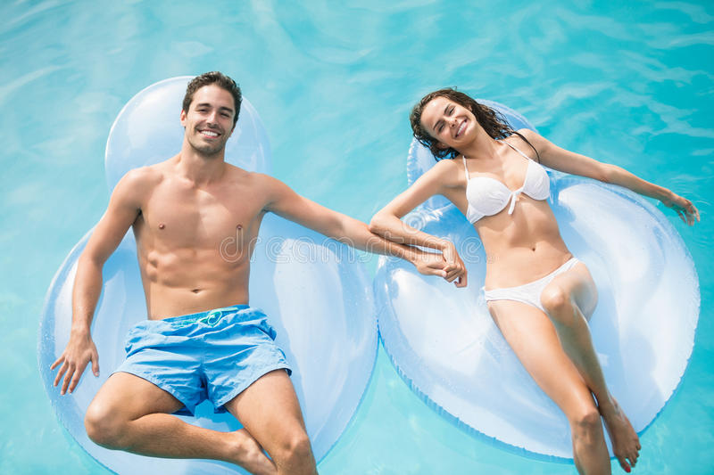 Happy couple relaxing on inflatable ring royalty free stock photography