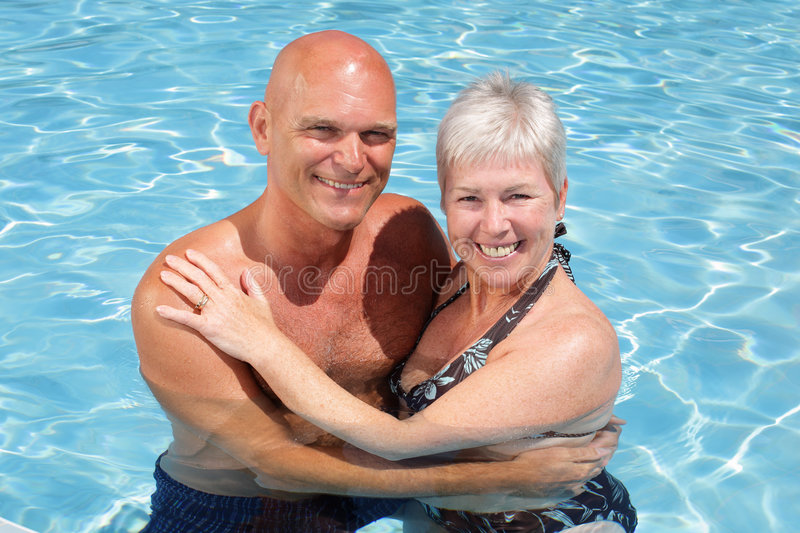 Happy couple relaxing by the pool. Enjoying summer holidays stock photos