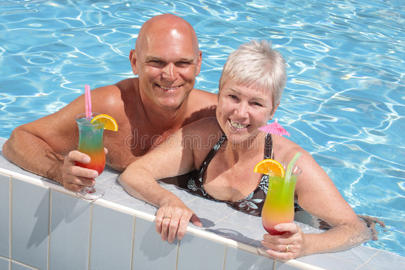 Happy couple relaxing by the pool. Enjoying exotic cocktails royalty free stock photos