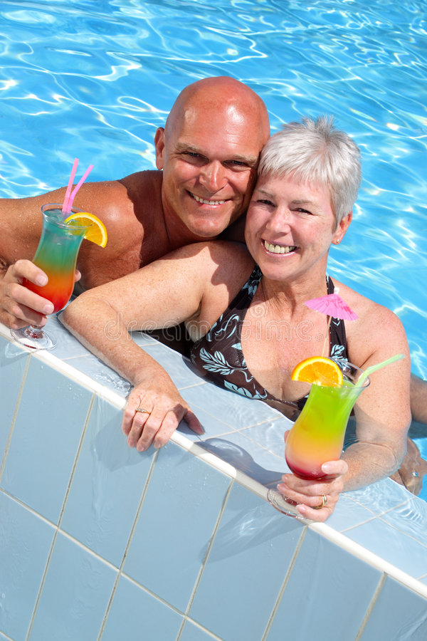 Happy couple relaxing by the pool. Enjoying summer holidays royalty free stock photography