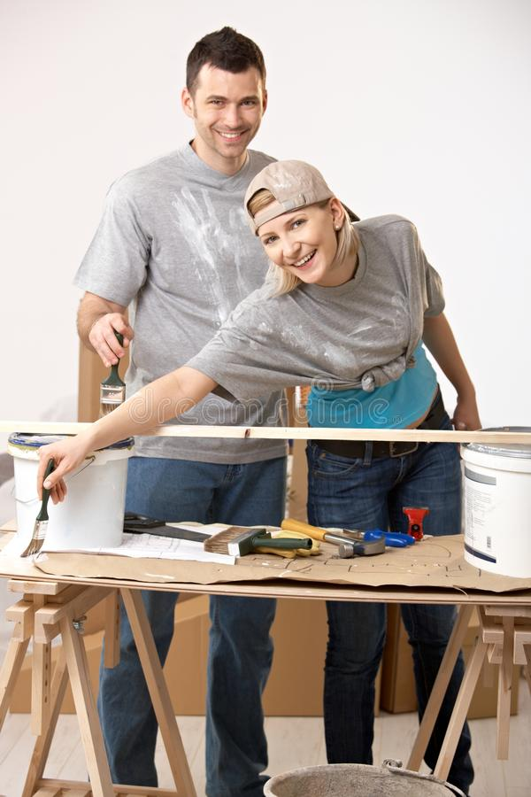 Happy couple renovating painting new home. Happy casual, caucasian couple busy renovating painting new home stock images