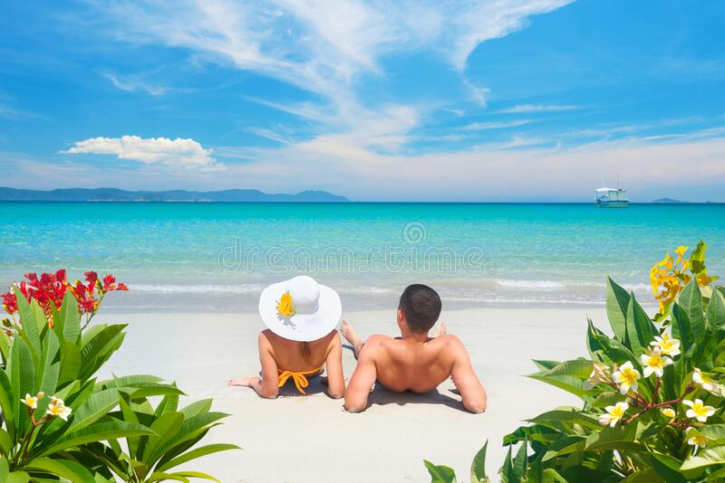 Happy couple resting on tropical beach on summer sunny day on background of beautiful blue sky and turquoise sea. royalty free stock photography