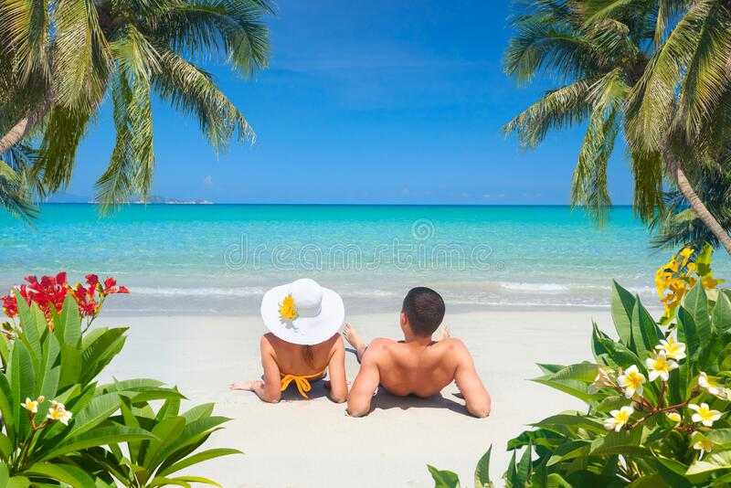 Happy couple resting on a tropical beach on a sunny summer day stock photos