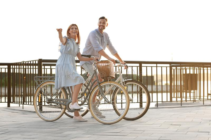 Happy couple riding bicycles outdoors stock photo