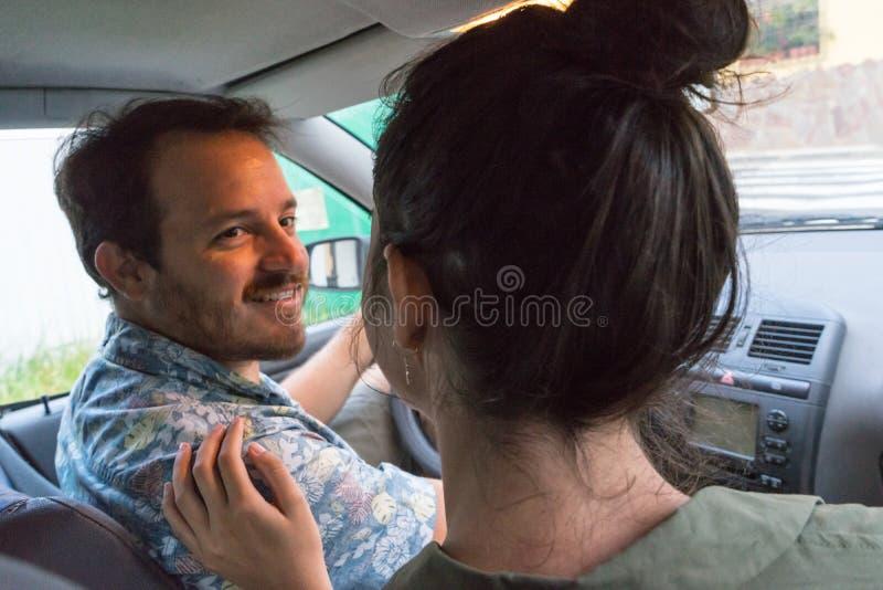 Happy Couple rijdt in de auto, zit in de auto, praat en luistert naar muziek De man rijdt met een auto die zijn passagier ziet stock afbeeldingen