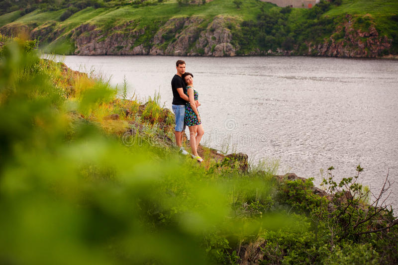 Happy couple by the river. Happy couple near the river in summer royalty free stock image
