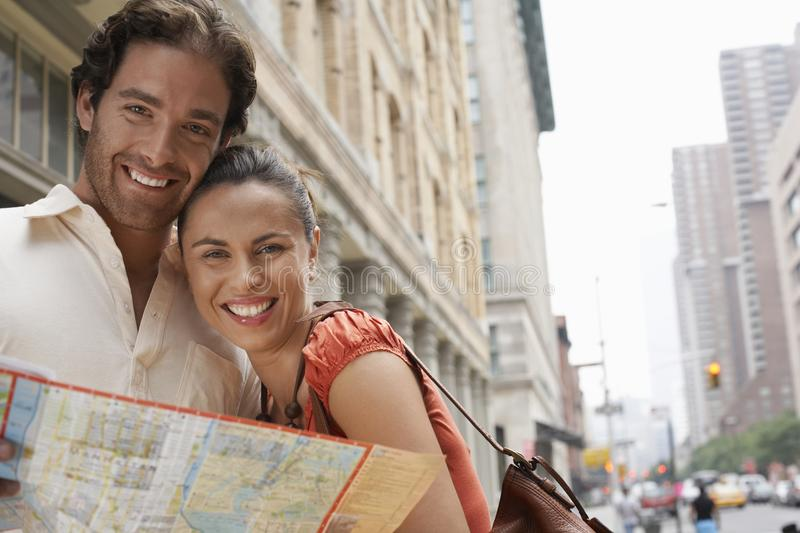 Happy Couple With Roadmap. Portrait of happy couple holding roadmap with building in the background royalty free stock photo