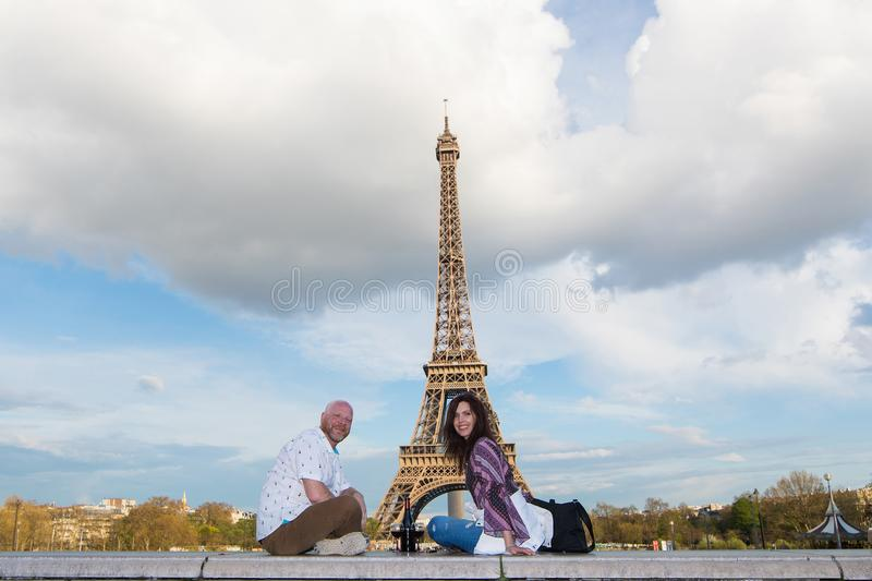 Happy couple on a romantic date at the Eiffel Tower in Paris, Fr. Happy Couple Sitting near the Eiffel Tower in Paris, France stock photos