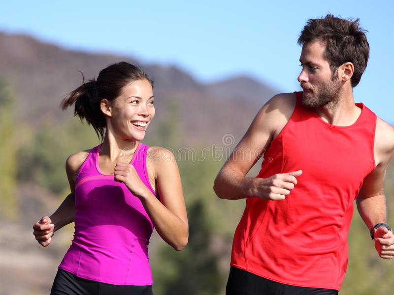 Happy couple running. And training outside. Healthy smiling young mixed-race Asian and Caucasian young couple exercising in nature
