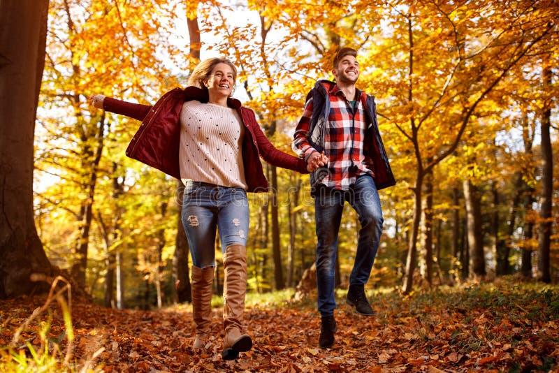 Happy couple running through park stock photo