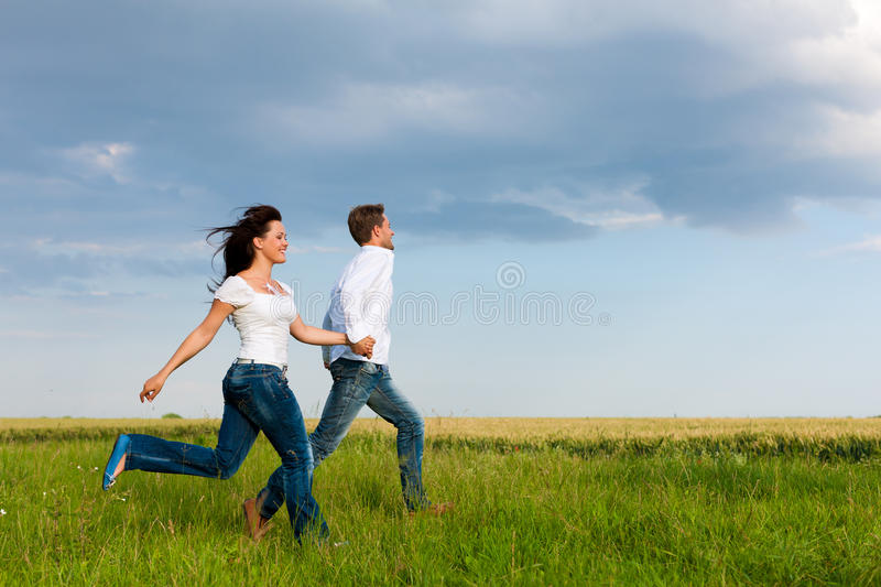 Happy couple running on a dirt road stock photos
