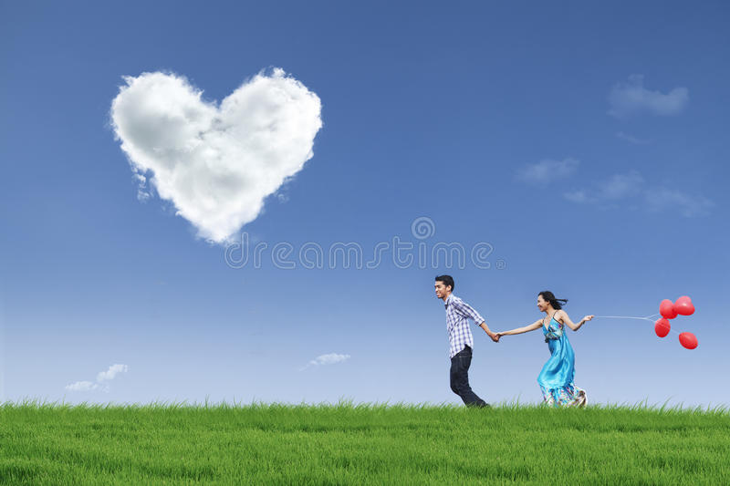 Download Happy Couple Running In Field With Balloons Stock Photo - Image: 27952352