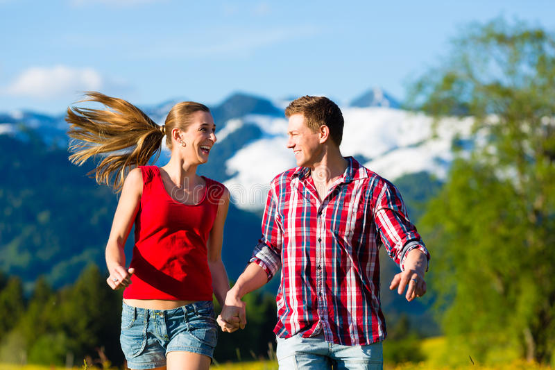 Couple running in the meadow with mountain royalty free stock photography