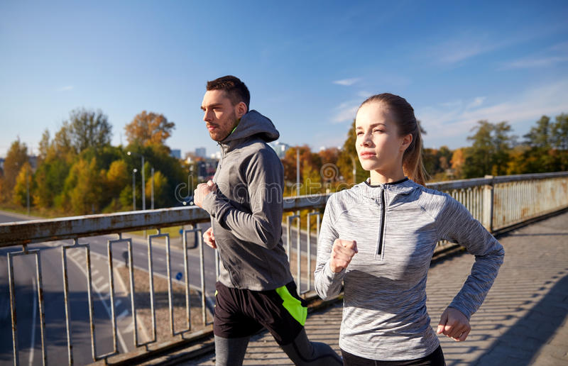 Happy couple running outdoors stock photography
