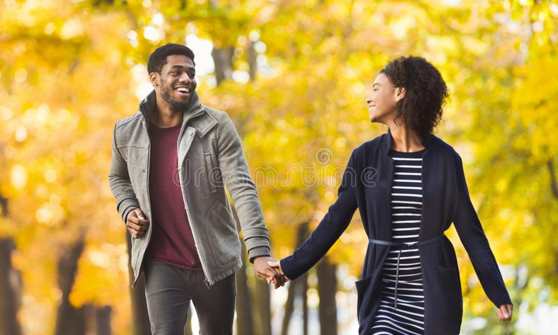 Happy couple running together in autumn park royalty free stock image