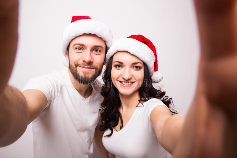 Happy couple in santa hats taking selfie picture from hands royalty free stock photography