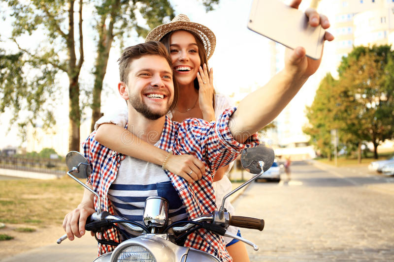 Happy couple on scooter making selfie photo on smartphone stock photography