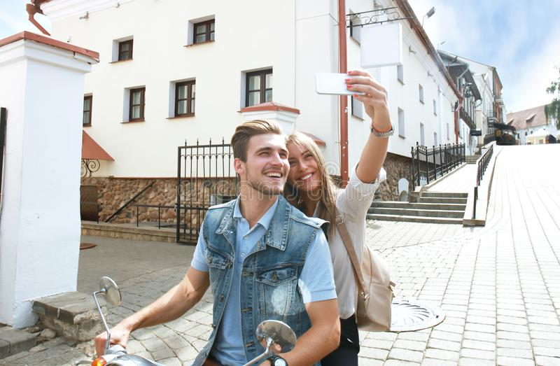 Happy couple on scooter making selfie photo on smartphone outdoors. Happy couple on scooter making selfie photo on smartphone outdoors royalty free stock image