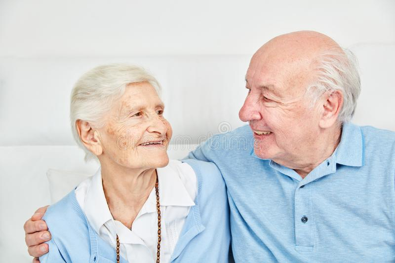 Happy couple seniors hugging each other at home. Happy couple seniors as a couple hugging on the couch at home stock photos
