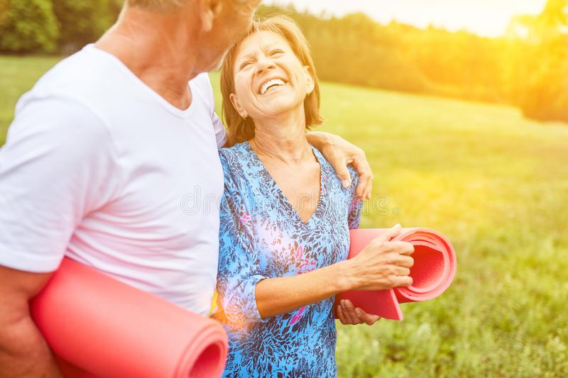 Happy couple seniors going for a walk. Happy couple of seniors while going for a walk in the park with gymnastics mat royalty free stock photo