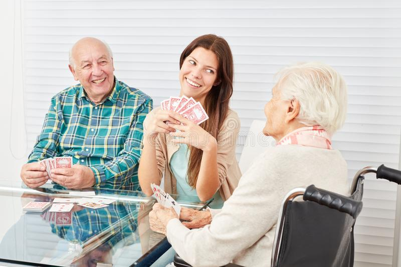 Seniors playing cards with granddaughter royalty free stock photos