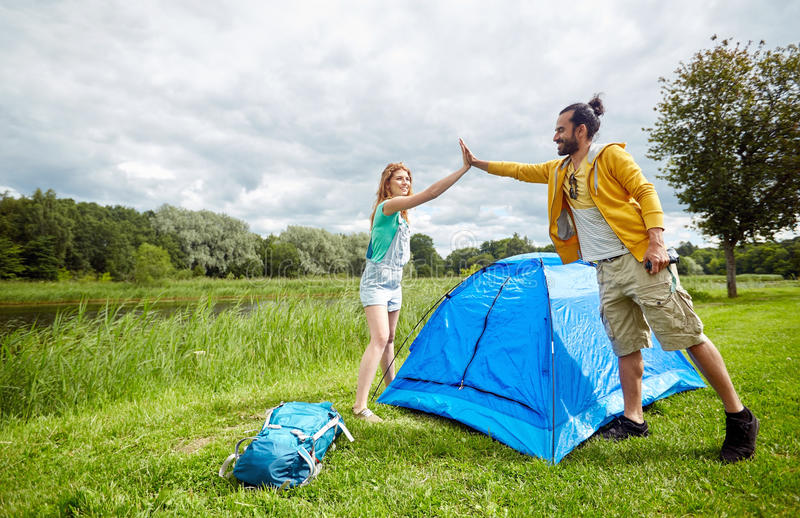 Happy couple setting up tent outdoors stock images