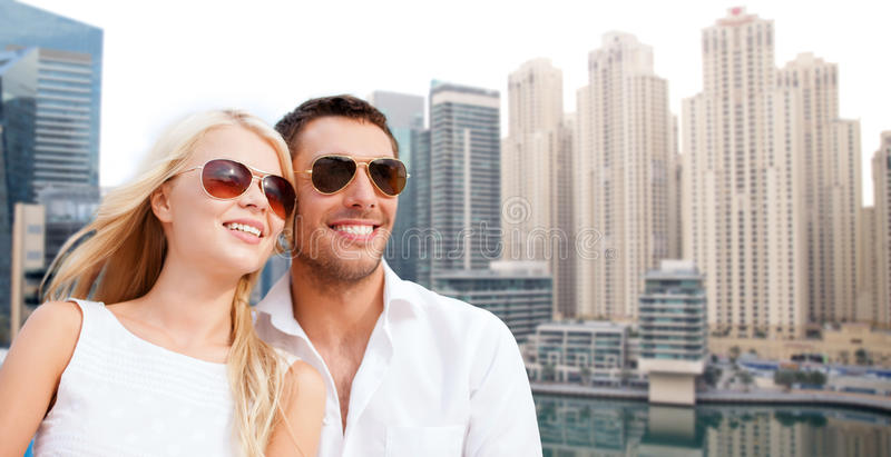 Happy couple in shades over dubai city background. Summer holidays, tourism, vacation, travel and dating concept - happy couple in shades over dubai city royalty free stock photography