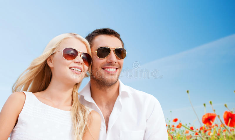 Happy couple in shades over poppy field background. Summer holidays, people and dating concept - happy couple in shades over blue sky and poppy field background royalty free stock photography