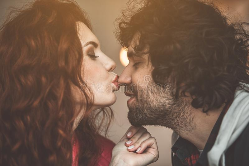 Happy couple sharing their love with each other. Love you. Sensual girl kissing nose of smiling guy with fondness. Their eyes are closed with pleasure stock photos
