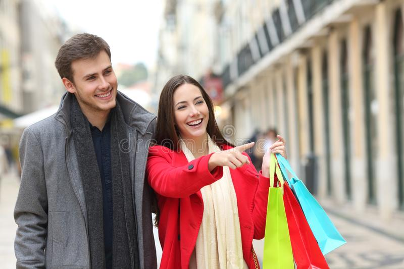 Happy couple shopping in an old town street. Happy couple shopping pointing at stores walking in an old town street stock photos